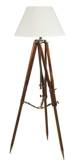 Features      Campaign Tripod Lamp is handmade from polished cherry wood, with brass hardware and saddler's leather straps.     Includes a cream fabric shade.     African, Hampton's & Traditional Styles.