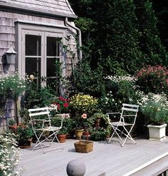 A lush container garden brings life to the sedate tones of this second-story deck. Flowers contrast with the monotone gray of the house, deck, and railing, but the space retains a peaceful and relaxed feeling.    The secret is a well-planned color scheme of mostly green and white, with splashes of yellow and hot pink.