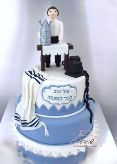 Two tiered cake with Tefillin, Tallit and a Bar Mitzvah boy embracing the Torah.