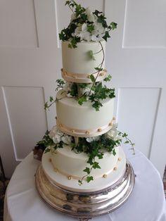 #vanillapodbakery elegant white tiered wedding cake with pillars and fresh foliage #wedding