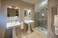 A shower room with double basins at The Barn & The Cowshed.