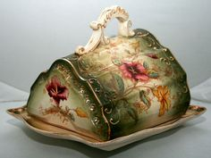"""C1900 Art Nouveau Cheese Keeper England - semi-porcelain cheese keeper, England, """"Rd.No.305511""""-marked-top & impressed-bottom, two piece-base and cover, scalloped cover fitted to shaped base, dark green and white background, raised scroll motif and open scroll handle, magenta and yellow transfer florals"""