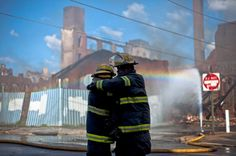 Firefighters greet each other in the aftermath of a fire in a warehouse in Philadelphia. Two firefighters were killed in the blaze.