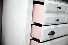 Love this surprising pop of pink in the dresser drawer of this baby girl nursery!