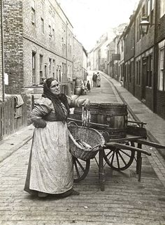 Woman selling fish from a barrel, London, c. 1910