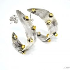 Kolczyki  wykonane ze srebra próby 925. Całość oksydowana, ozdobione 24 k złotem. Zapinane na sztyfty.