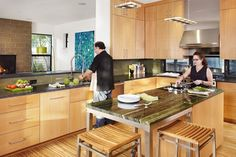 Blonde-colored wood cabinets and floors give this kitchen a monochromatic, unified look. Green stone countertops on the island and an olive tile backsplash inject a small does of color. Wood slat bar stools sit underneath a rolling island. Contemporary Kitchen Cabinets, Wood Kitchen Cabinets, Contemporary Kitchen Design, Floating Shelves Bedroom, Floating Shelves Kitchen, Blue Kitchen Decor, Kitchen Decor Themes, Open Concept Kitchen, Kitchen Layout
