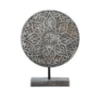 Ornate Disc Sculpture – 37 x 52cm Taking influence from traditional cast iron sculptures, this stunning ornament is a wonderful centrepiece for a sideboard or mantelpiece. Made from terracotta, intricate patterns weave their way around the centre disc, with weathered and worn edges giving it a vintage, almost antique look.Depth: 39 CMHeight: 52 CMMaterial Content: TerracottaWidth: 37 CM