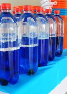 And MY FAVORITE PART!! Ocean in a bottle. I used Target's Market Pantry brand flavored water bottles because I liked the size and shape. They are filled with two orange fishes-like the ones on the table cloth in the previous picture water with blue food coloring, and baby oil. I hot glued the lids on