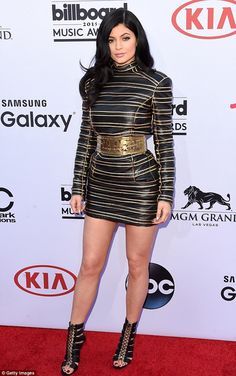 Legging it: Kylie, 17, opted for a black and gold mini dress with high neckline and thick ...