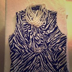 Zebra quarter button blouse. Sleeveless blouse from Express. Button up top half. Buckle in front. It zips open in the side to put on and off. Looks great with a pencil skirt. Express Tops Blouses