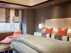 The warm gray walls create a strong background against the light and crisp cream-colored bedding. Pops of coral bring a bright splash of color to the bedroom. Design by Ana Donohue