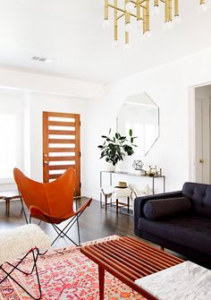 White walls, orange chair, black couch, printed pink and orange rug, brown coffee table, octagon shaped mirror, silver table, and wooden door