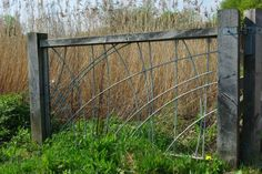 Oak gate leaf with steel 'reed' pattern in-fill panel with actual reeds behind. Design : Kevin Barton