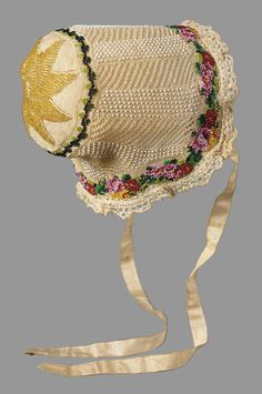 Infant's cap, German or Austrian early 19th century Knitting and beading Fine cream colored cotton knitted in openwork design with wreath and star at back and floral border worked with pink, orange, yellow and green beads. Edged with bobbin lace, two cream colored ribbon ties.