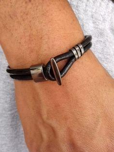 Pulseira masculina em couro original preto, com metais em fumê e fecho em gancho também fumê. R$ 35,00