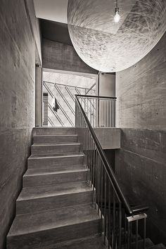 Dramatic pendant light and the concrete backdrop create a monochromatic setting for the staircase