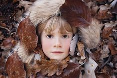 A girl's face in autumn leaves