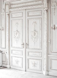 Fabulous double wooden doors with tone on tone white and lots of carving detail.