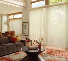 Hunter Douglas Luminette White Vertical Blinds - this living room setting uses vertical blinds for their sliding glass door and picture window for privacy and light control. Note the open windows near the ceiling allow ambient light in at all hours of the day, which is an option to consider, especially if the room faces toward the north. Modern coffee table looks great with select flowers or artwork.