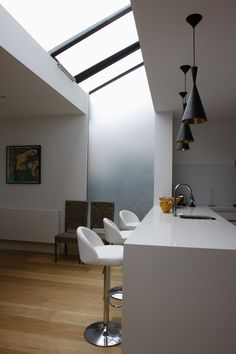 Auto-opening rooflight in glass roof with stepped edge translucent glass window above kitchen.