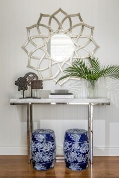 Beautiful foyer vignette with silver petal shaped wall mirror pairing with a modern chrome based, marble topped console. The console is topped with three wooden decorative objects, stacked books and a glass vase full of palm leaves. A pair of blue and white floral print garden stools sit beneath the console. The walls are paneled in tongue and groove and the floors finished with hardwood.