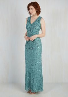 Slip into this decadent aqua gown, and fame will be sure to find you! As camera flashes illuminate the intricate beading, sequins, and sweeping sheer back panel of this V-neck dress, you strike a pose of poise, knowing that your red carpet look was a snap to create.