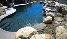 Pool with a little stream beside it (Backyard Beach Pool Service Rate Information)