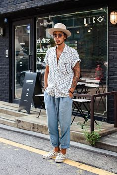 Comfy street Style. Loose V neck shirt, slightly baggy light denim ankle grazer jeans, shoes made for walking and a hat to protect from the sun.