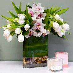 Delicate pink Orchids and white Ranunculus in a square glass vase with a bed of rocks from Manhattan Beach Florist. This wild design focuses your attention on the delicate beauty of the Orchid, and it makes an excellent gift for pretty much anyone.Manhattan Beach Florist is the best online florist for the Beach Cities area, offering a wide variety of high-end blooms for every occasion. Order flowers online from Manhattan Beach Florist for same day local flower delivery from conveniently ...