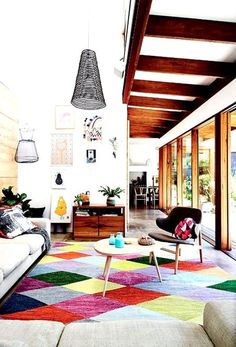 Nordic style living room with bold rug and accents in bright colours, bold prints, colour blocking