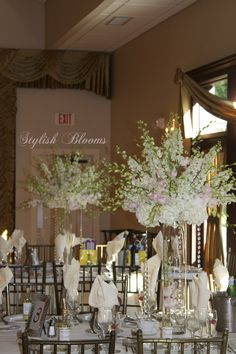 Pink Dendrobium orchids, white larkspur and white hydrangea centerpieces with hanging crystals