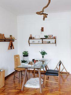 Comedor con mesa de vidrio y sillas dispares en un departamento de pocos metros con detalles rústicos en madera y textiles naturales. Parte del Dossier Sub 35 de Living.