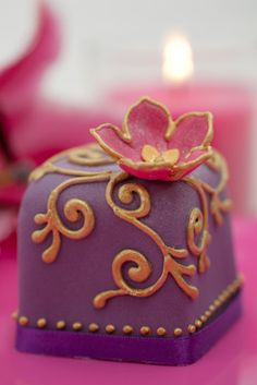 """""""Rachelles Beautiful Bespoke Cakes: Indian Dream - £10.00 -  Vibrant colours with hand painted gold detail, a beautiful Bollywood inspired cake. Mix and match with a co-ordinating cupcake design or fresh flowers to create a stunning centrepiece. Mini cakes are available in fruit, lemon, vanilla or chocolate.  For an extra £2-00 we can box your cakes individually and tie with satin or organza ribbon to match."""""""