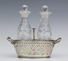 Kristallen olie-azijnstel, Louis XVI, in ovaal mandvormige houder met opengezaagde vlechtmotieven, fijne muntrand en twee oren gevormd door bladranken. Mt. Antoni Bolsius, Den Bosch, jl. 1785