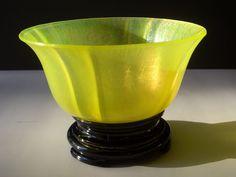 Tiffin vaseline stretch glass bowl on black glass stand.