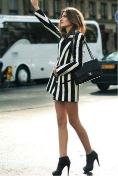 Acheter la tenue sur Lookastic:  https://lookastic.fr/mode-femme/tenues/blazer-croise-a-rayures-verticales-blanc-et-noir-bottines-en-daim-cartable-en-cuir-noir/1648  — Bottines en daim noires  — Cartable en cuir matelassé noir  — Blazer croisé à rayures verticales blanc et noir