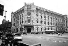 La vida cotidiana frente al Palacio de Correos alrededor de 1930. Este inmueble es obra de Adamo Boari y fue inaugurado en febrero de 1907, ocupando el espacio donde había estado el Hospital de Terceros de San Francisco. A la izquierda se aprecia el Palacio de Minería, que entonces albergaba la Escuela Nacional de Ingenieros.