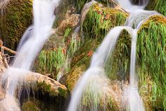 Water cascade flowing over rocks covered with grass and moss.