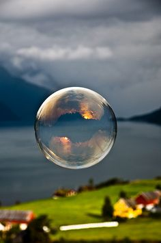 Morning light reflected in a soap bubble over the fjord.