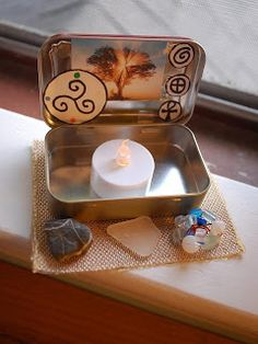 Altoid Tin Traveling Altars - This one is pretty and simple, with a candle and some precious stones.