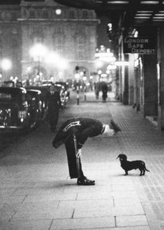 "A hotel commissionaire talking to a small dachshund dog in Piccadilly Circus, London. Original publilshed in Picture Post ""In The Heart of the Empire "" 1938 Photo by Kurt Hutton"