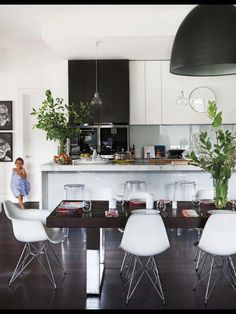 Black and white kitchen with glass pendants over island bench and solid pendant over table