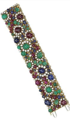 GEM-SET AND DIAMOND BRACELET Designed as a wide articulated band set with cabochon emeralds, rubies and sapphires, accented with brilliant-cut diamonds, mounted in yellow gold and platinum, length approximately 183mm, French import marks.