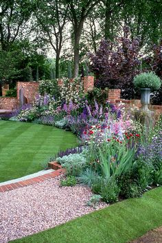 Beautiful walled garden...Glorious gorgeous flower perennial garden with lawn, steps, Delphinium, Knautia, Salvia, climbing vine on brick wall, pot container.  2003 Chelsea Flower Show Silver Gild medal winner