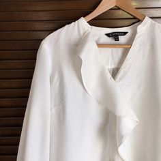 White Express blouse Worn once. Blouse is flowy and elegant. The v-neck and scalloped ruffle draws your eye downward for a very slimming look. Blue skirt also for sale in my closet. Express Tops Blouses