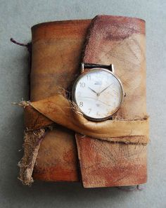 worn leather journal and wrist watch