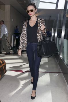 Miranda Kerr amped up her travel style with a leopard Stella McCartney cardigan ($1,128), glitter Miu Miu shades ($390), and her trusty Givenchy tote after touching down at LAX.
