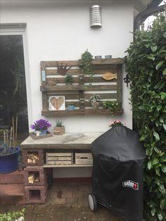 Grilltisch mit Aussparung für einen Kugelgrill, Betonplatte, Pflanzsteine und Holzregal, Palettenregal an der Wand