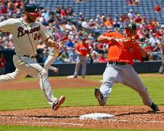 Atlanta Braves' Evan Gattis wins a foot race against the Miami Marlins pitcher Henderson Alverez reaching to first base safely on a ground ball during the fourth inning of a baseball game .